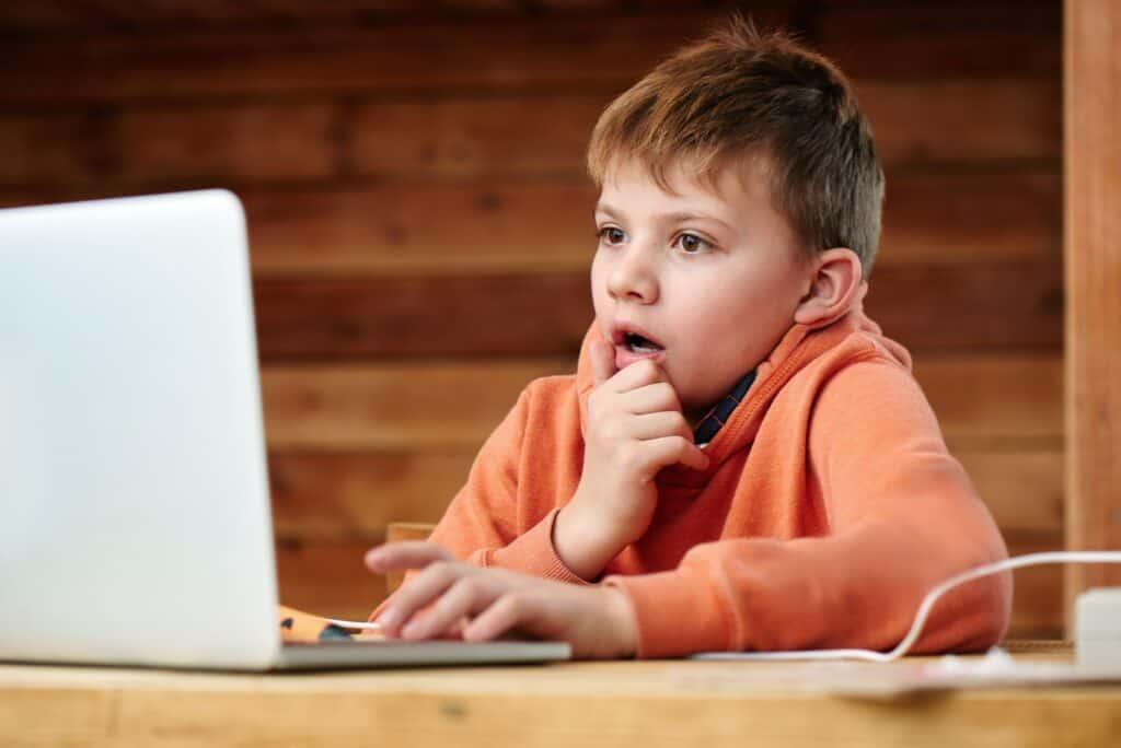 Boy looking shocked at computer screen