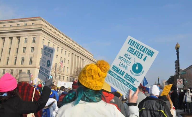 """Woman holding sign that says """"fertilization creates new distinct living unborn human beings"""""""